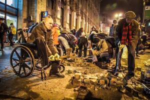 A man in a wheelchair is digging out pavement stones, used  by protesters for defense against  riot police deadly attacks. @Mustafa Nayyem